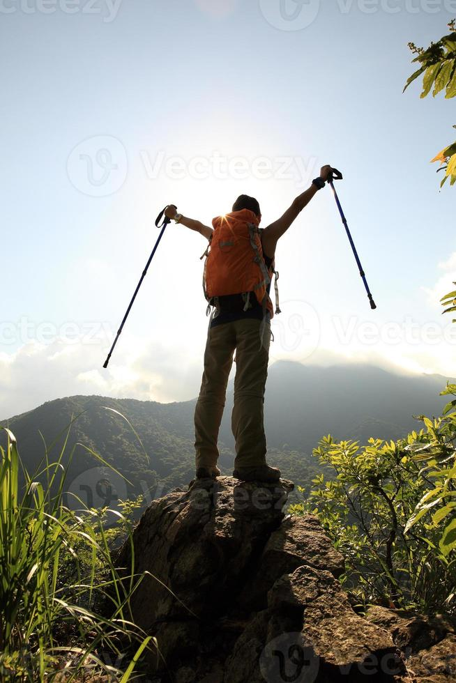 cheering woman hiker open arms at mountain peak cliff photo