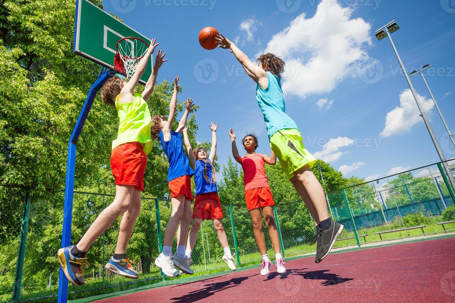 Children jump for ball during basketball game photo