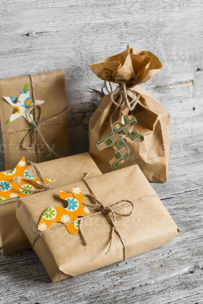 Regalos de navidad en papel kraft sobre la superficie de madera brillante foto