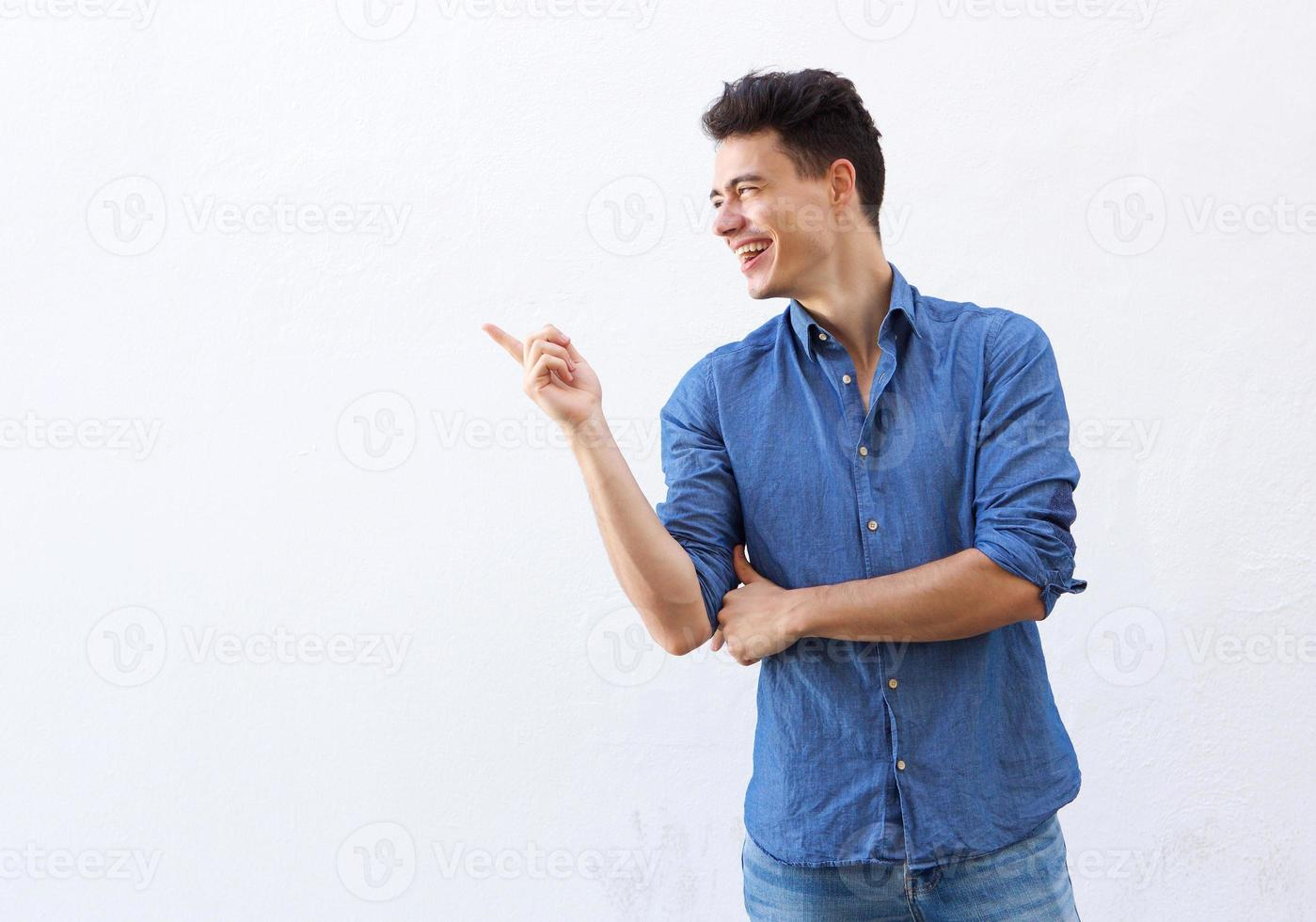 Smiling young man pointing finger to copy space photo