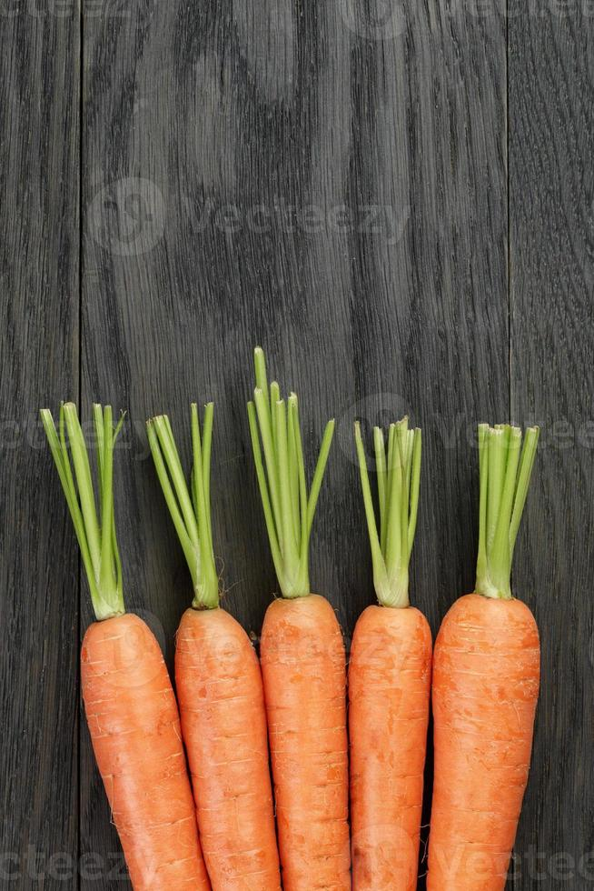 fresh carrots on old oak table with copy space photo