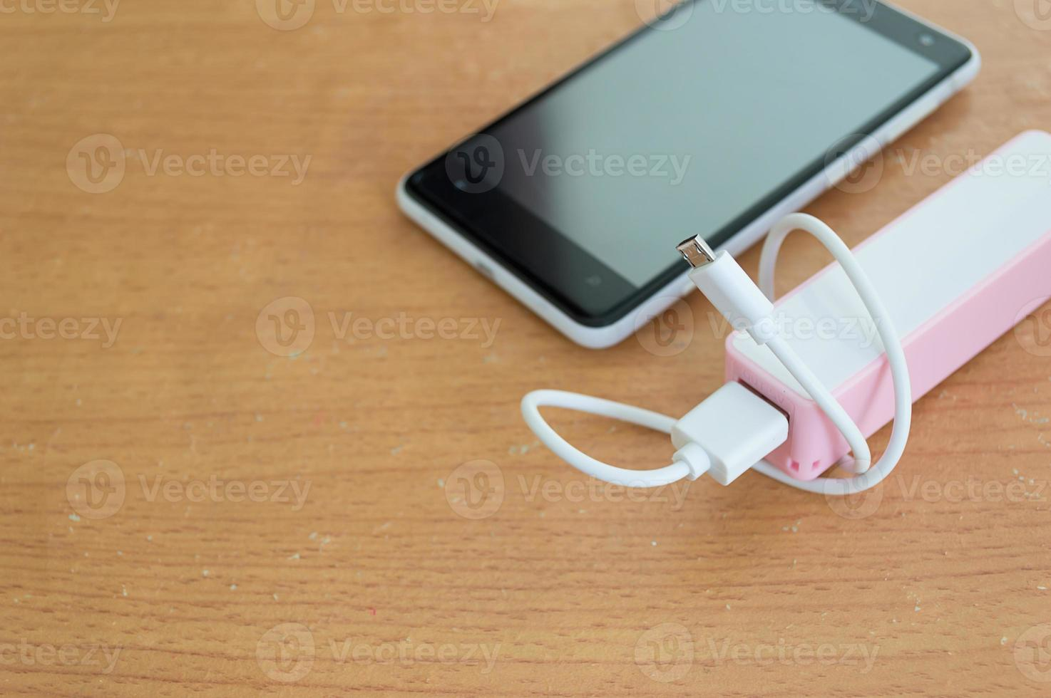 Smartphone with powerbank on wood desk and copy space photo