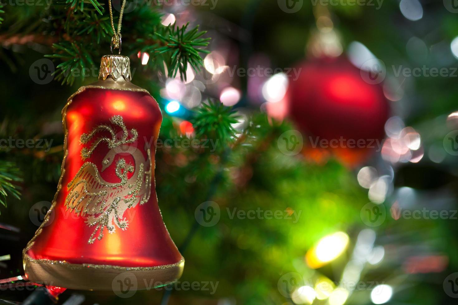 Adorno de navidad con árbol iluminado en el fondo, espacio de copia foto