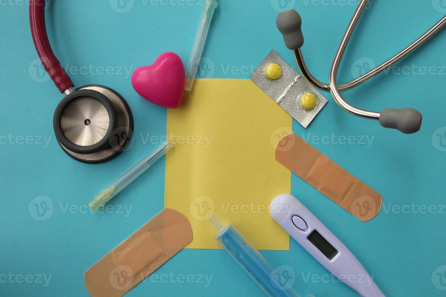 Pill, syringe, needle, medical thermometer, bandage, sthetoscope and copy space photo