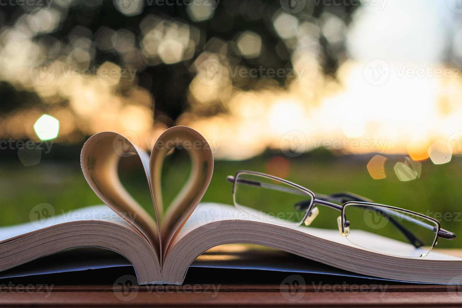 Close up book and glasses on table in sunset time photo