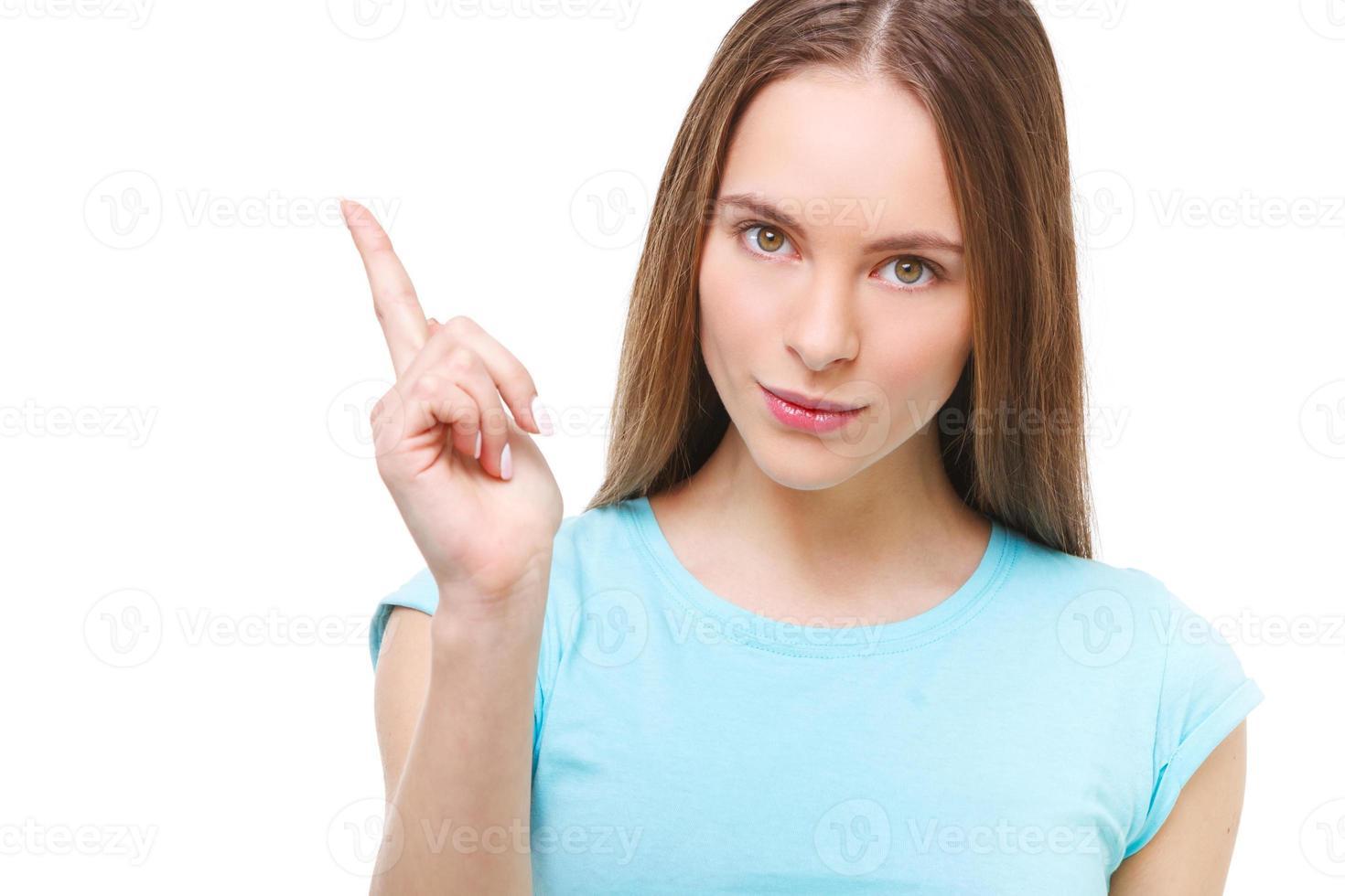 Mujer joven que señala con su dedo en el espacio de la copia aislado. foto