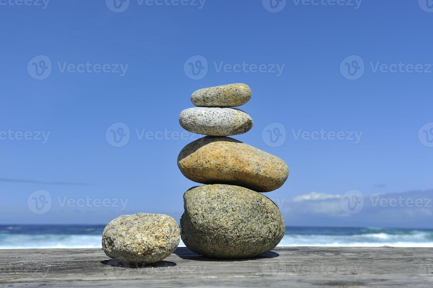 Zen stones stacked at beach waves blue sky copy space photo