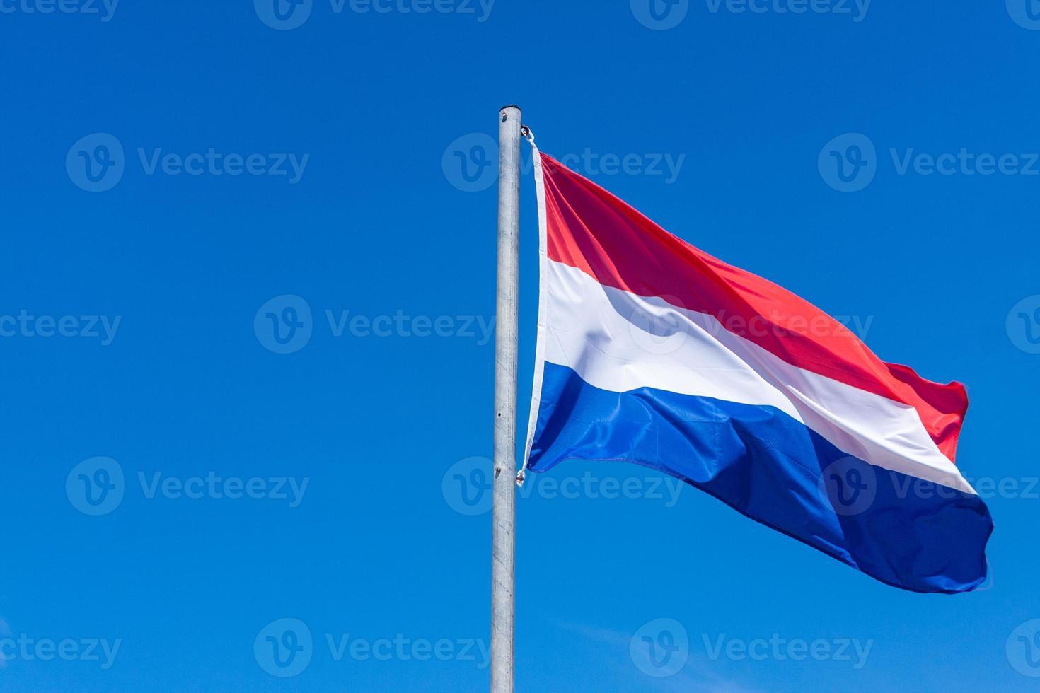 Dutch flag against blue sky photo