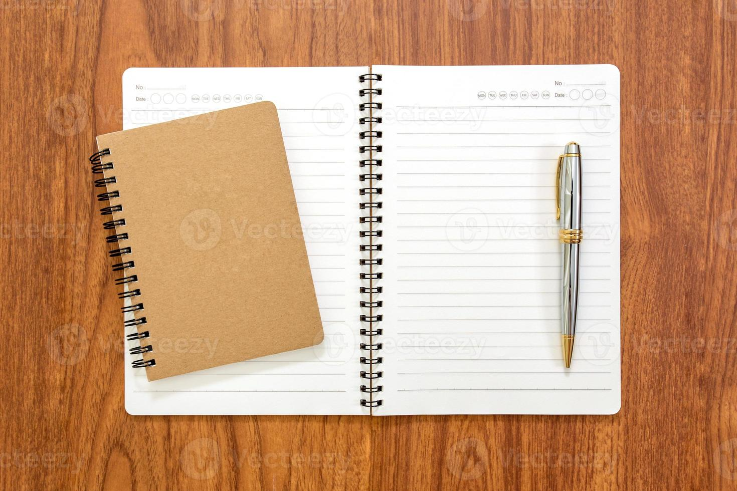 Blank notebook with a pen on wood background photo