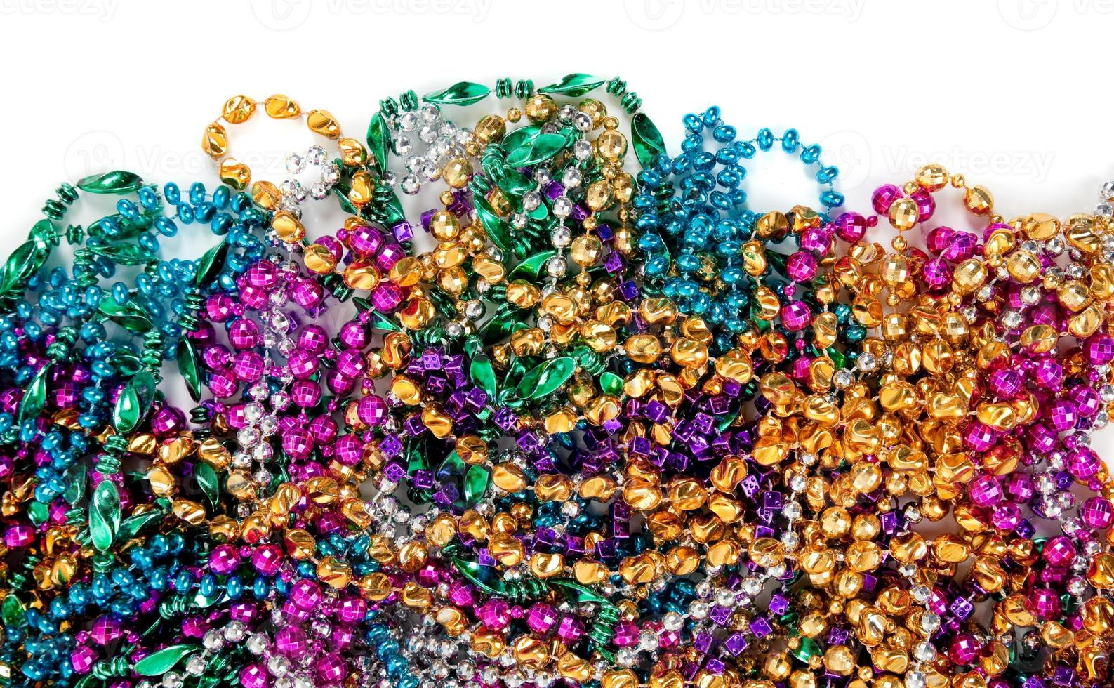 Mardi gras beads on white with copy space photo