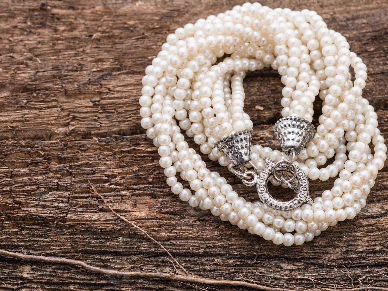 Pearl necklace on wood background with copy space photo