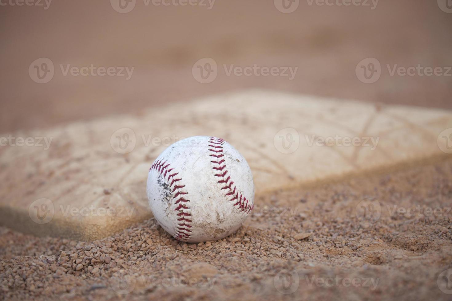 Selective focus low angle of grungy baseball and base photo