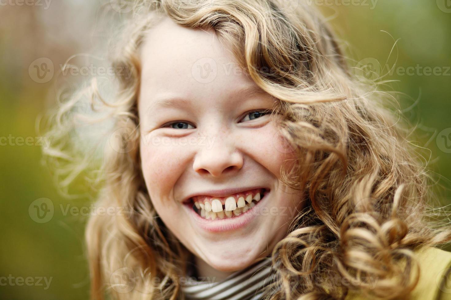 Outdoor portrait of happy blond girl photo