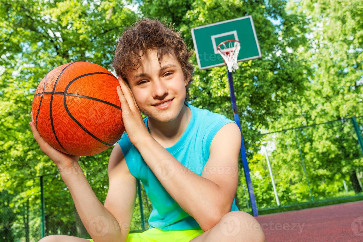 Happy boy sits on playground, holds ball near face photo