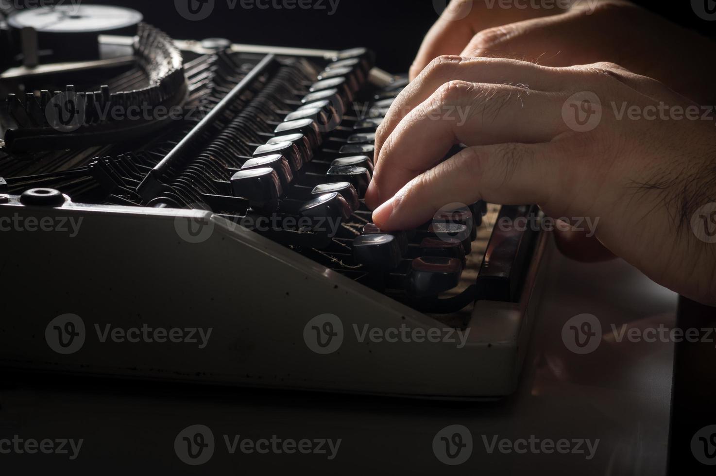 manos humanas escribiendo con máquina de escribir foto