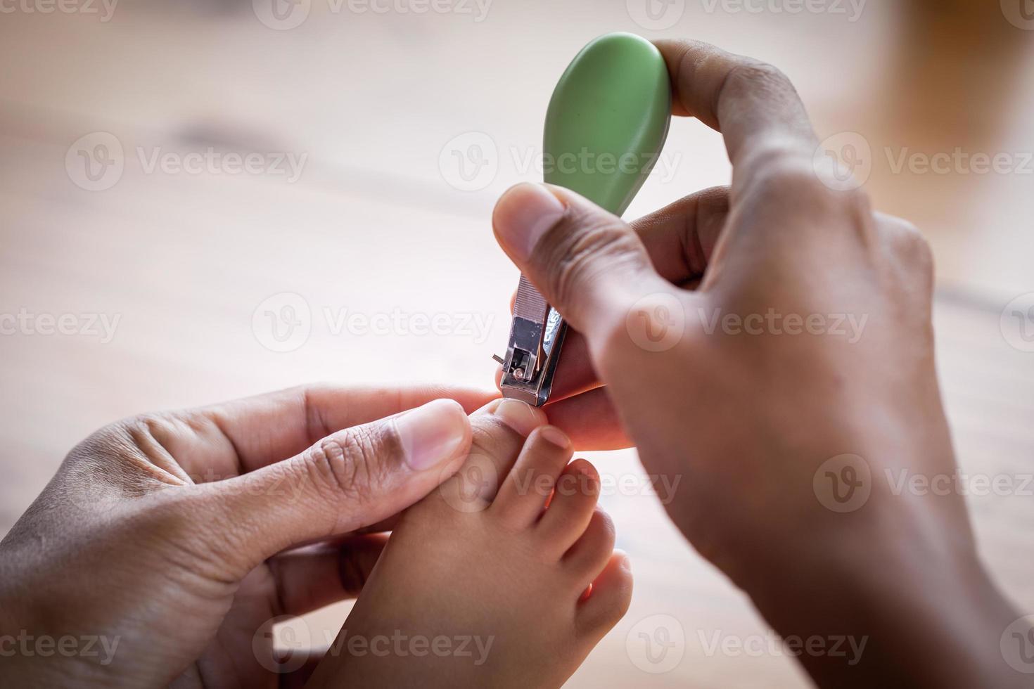padre cortando las uñas de los pies para su bebé foto