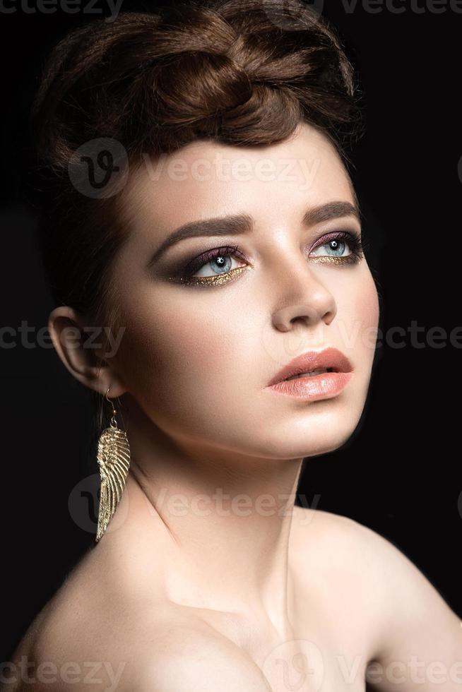 Hermosa chica con maquillaje brillante y peinado de noche. foto