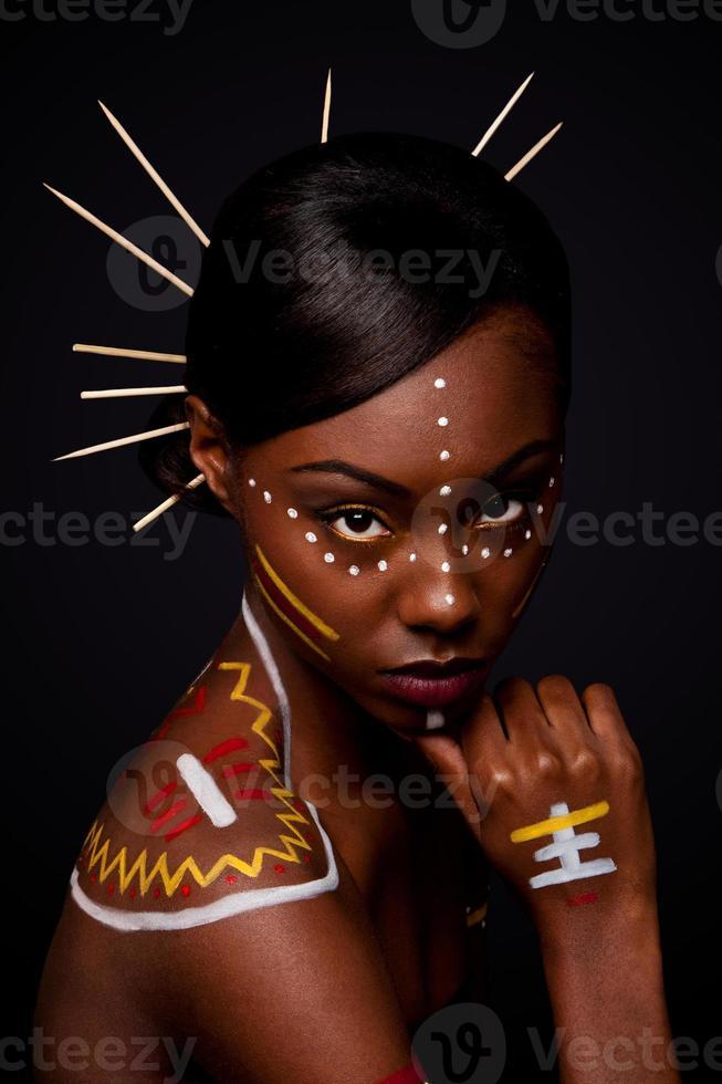 Retrato de mujer de hombro desnudo en maquillaje tribal foto