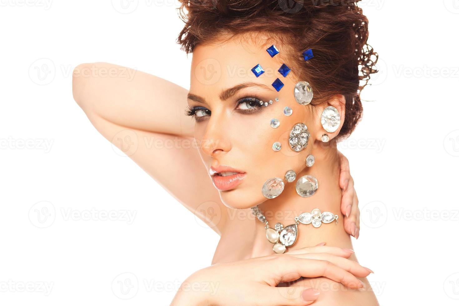 Retrato de una hermosa niña con diamantes en la cara foto