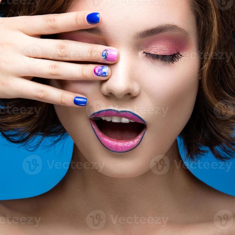 Chica hermosa modelo con maquillaje brillante y esmalte de uñas de colores. foto