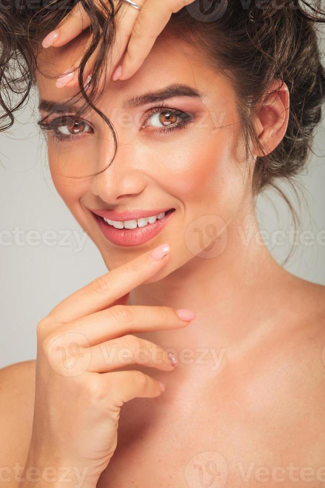 Retrato de la bella modelo tocando la cara y arreglando el cabello foto