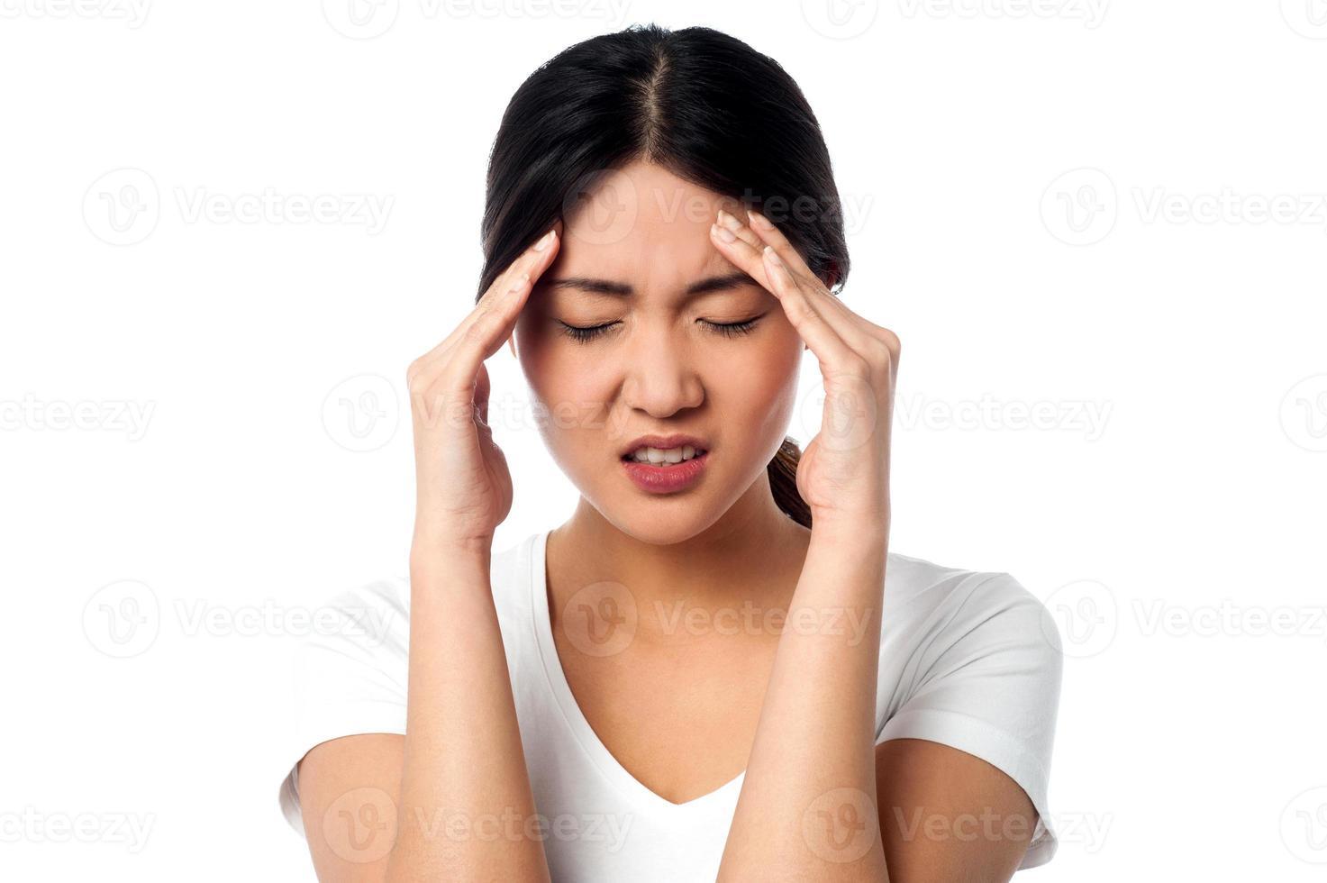 mujer joven que tiene dolor de cabeza foto
