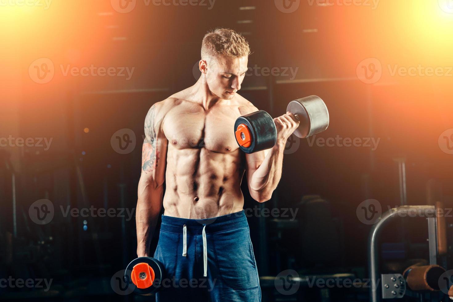 culturista muscular atleta entrenando con pesas en el gimnasio foto