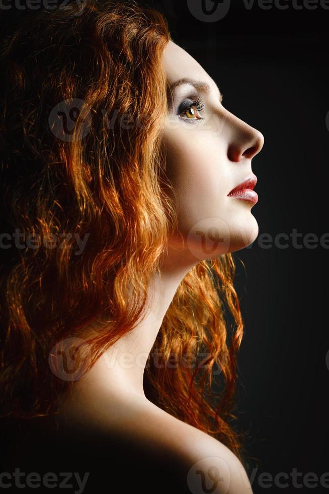 Closeup retrato de estudio de mujer hermosa pelirroja. vista de perfil foto