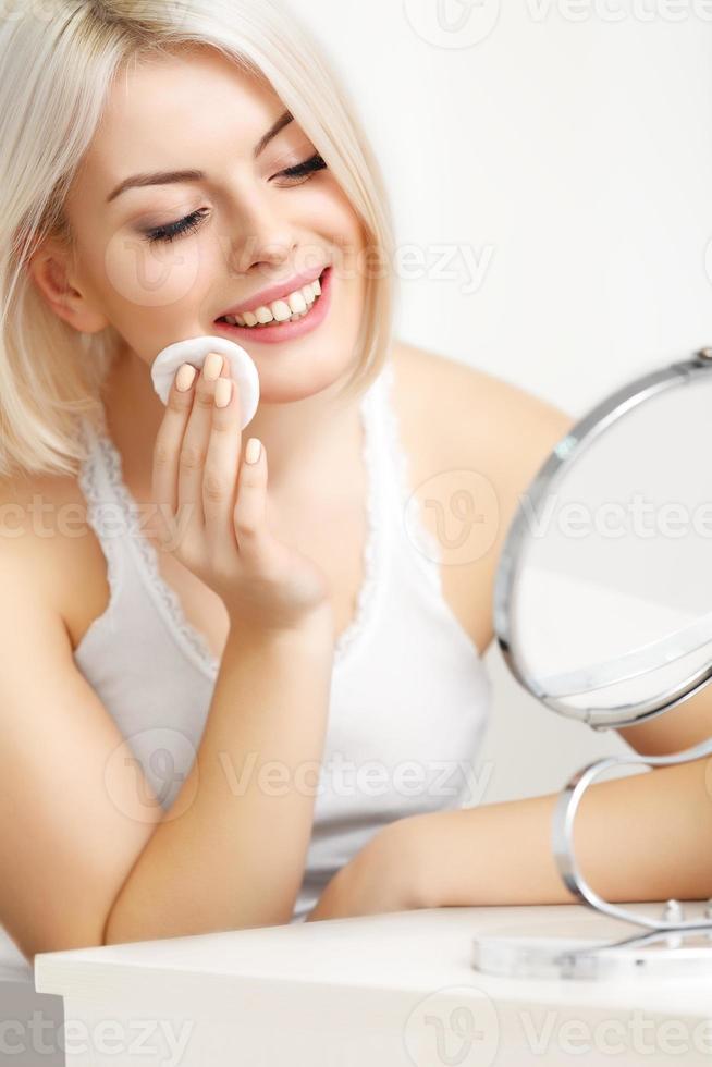 Hermosa mujer haciendo maquillaje diario. esponja cosmética foto