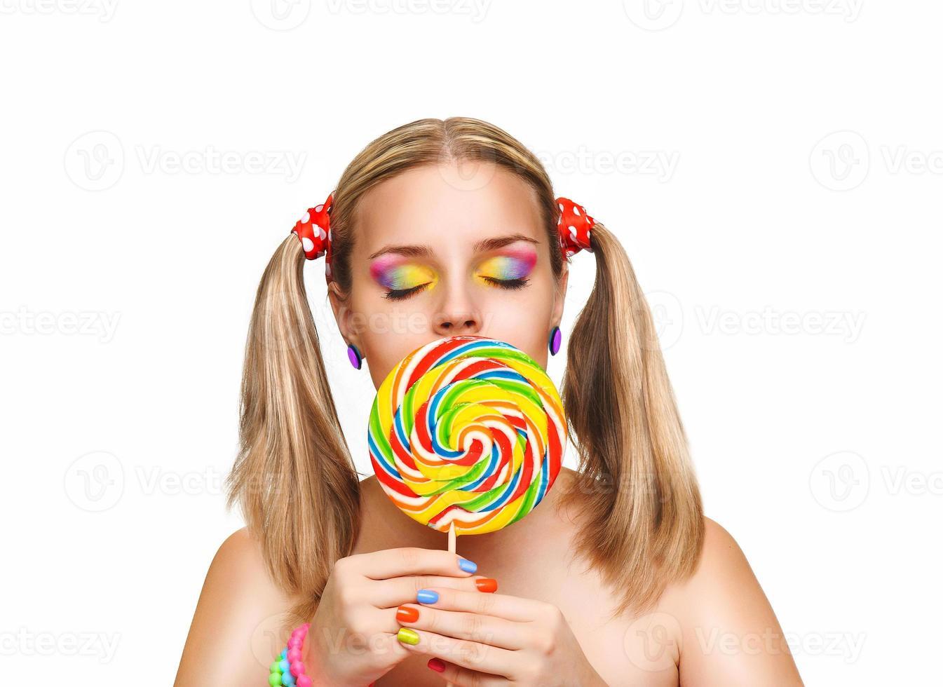 Niña comiendo paleta de colores. pirulí. foto