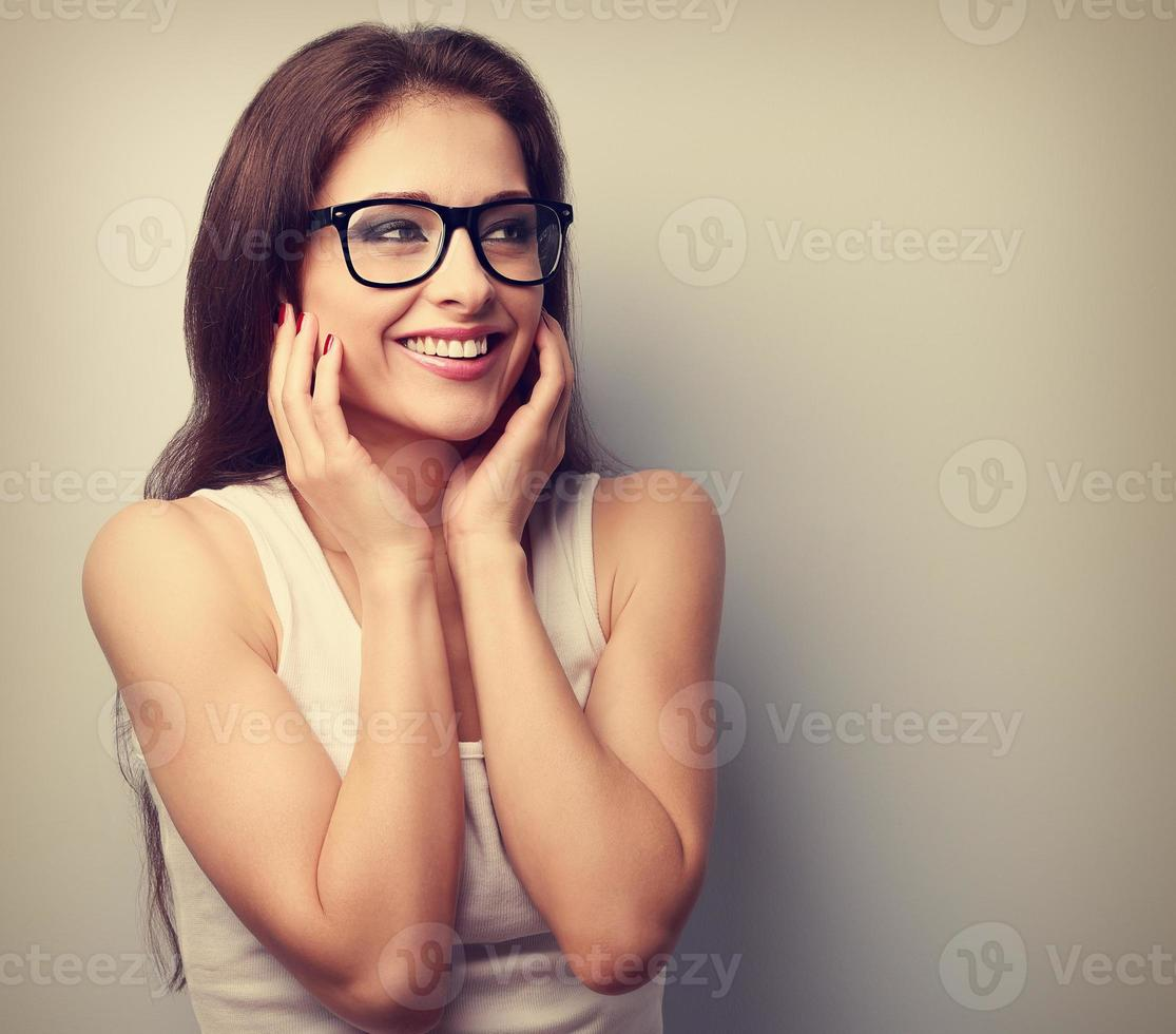 Happy laughing young casual woman holding hands the face photo