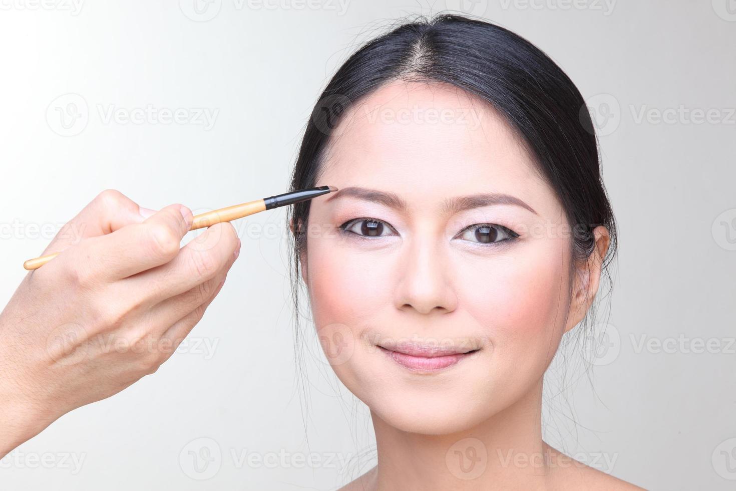 maquilladora profesional haciendo maquillaje modelo glamour en el trabajo foto
