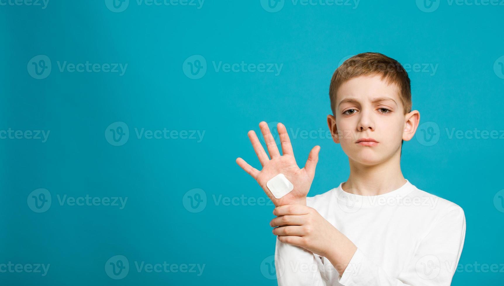 niño infeliz con yeso adhesivo blanco en la mano foto