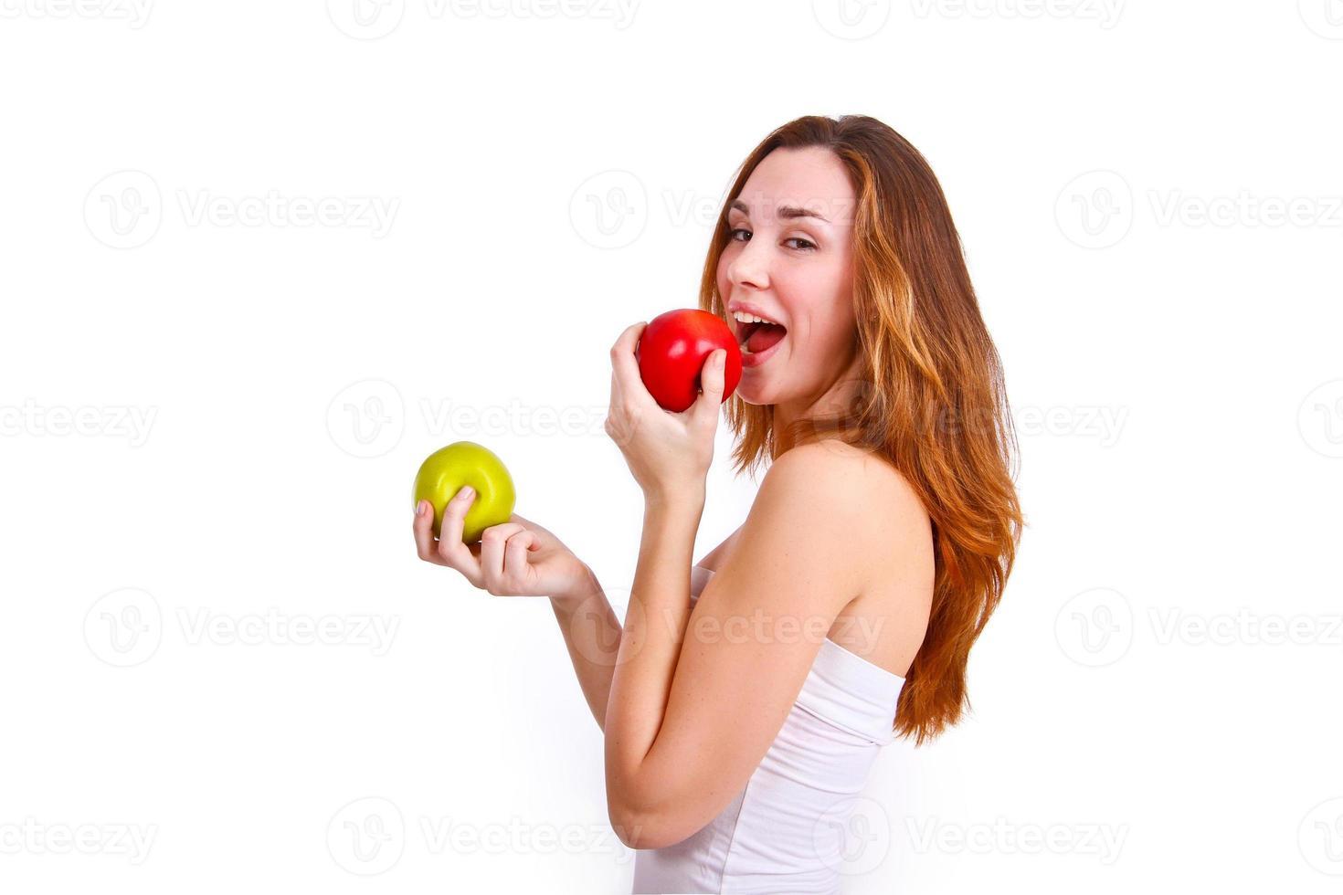 Chica atractiva comiendo manzanas sobre fondo blanco. foto