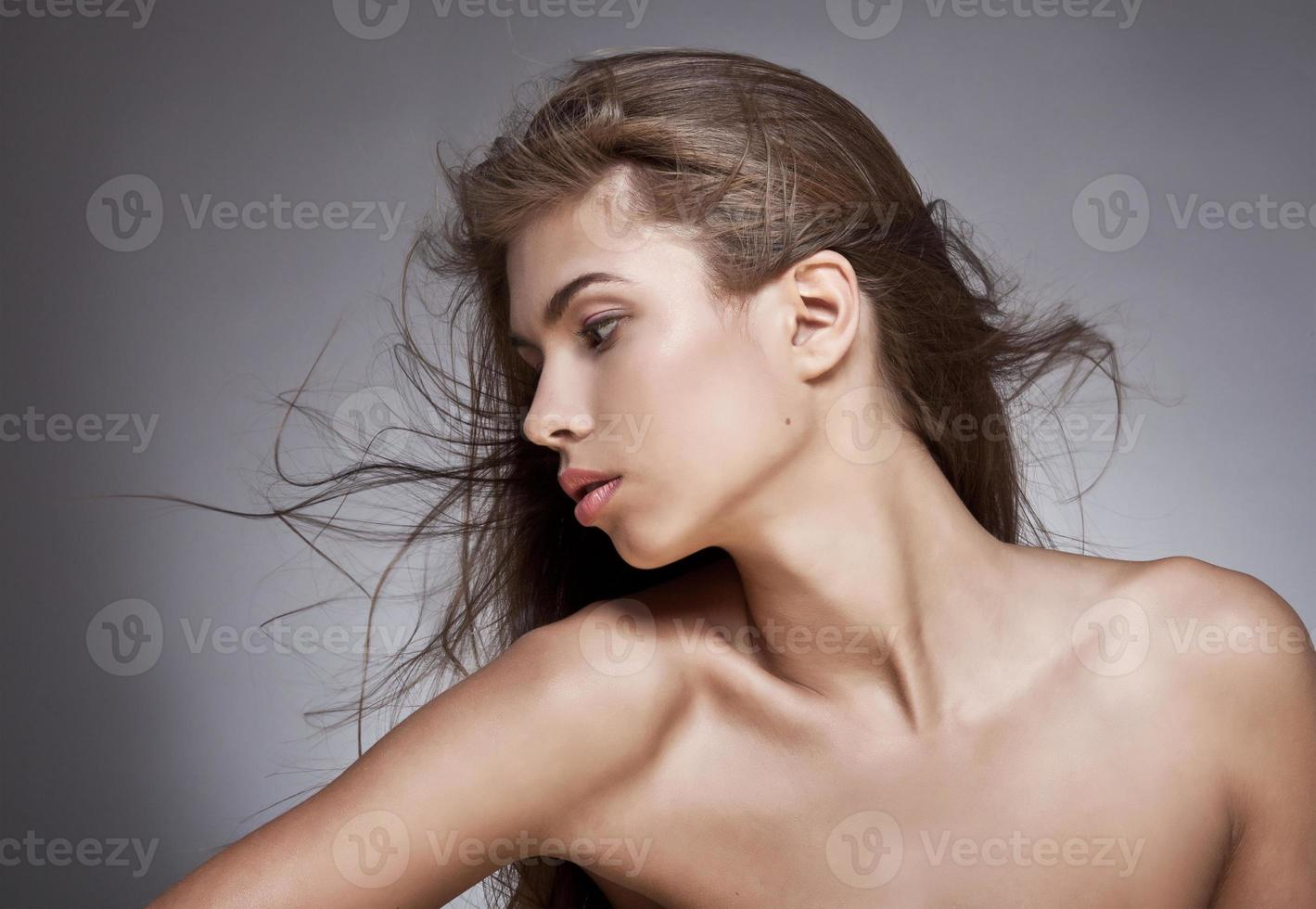 Beautiful woman with fluttering hair. On dark background. photo