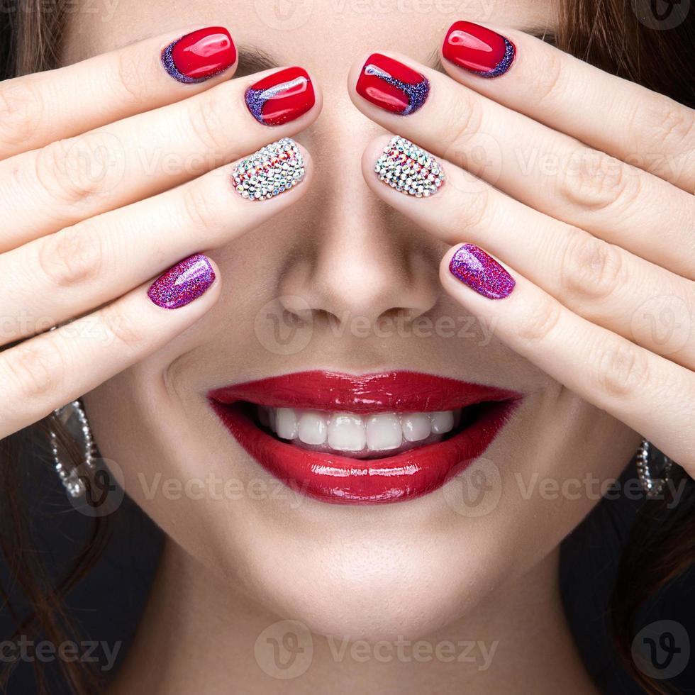 Chica con un brillante maquillaje de noche y manicura con pedrería. foto