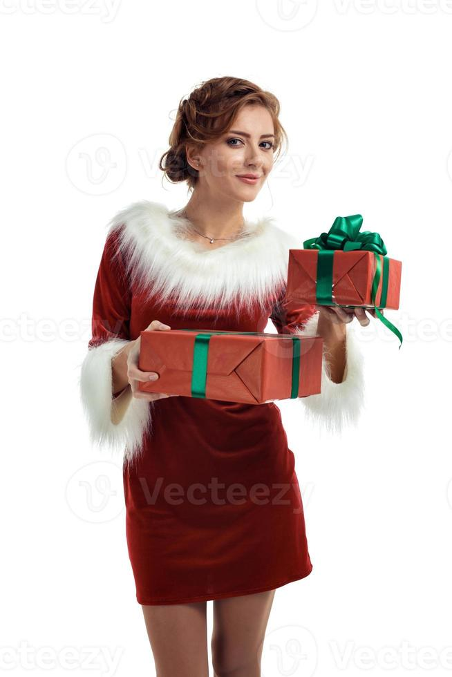 Smiling model posing in studio with gifts. Beautiful Santa Girl. photo