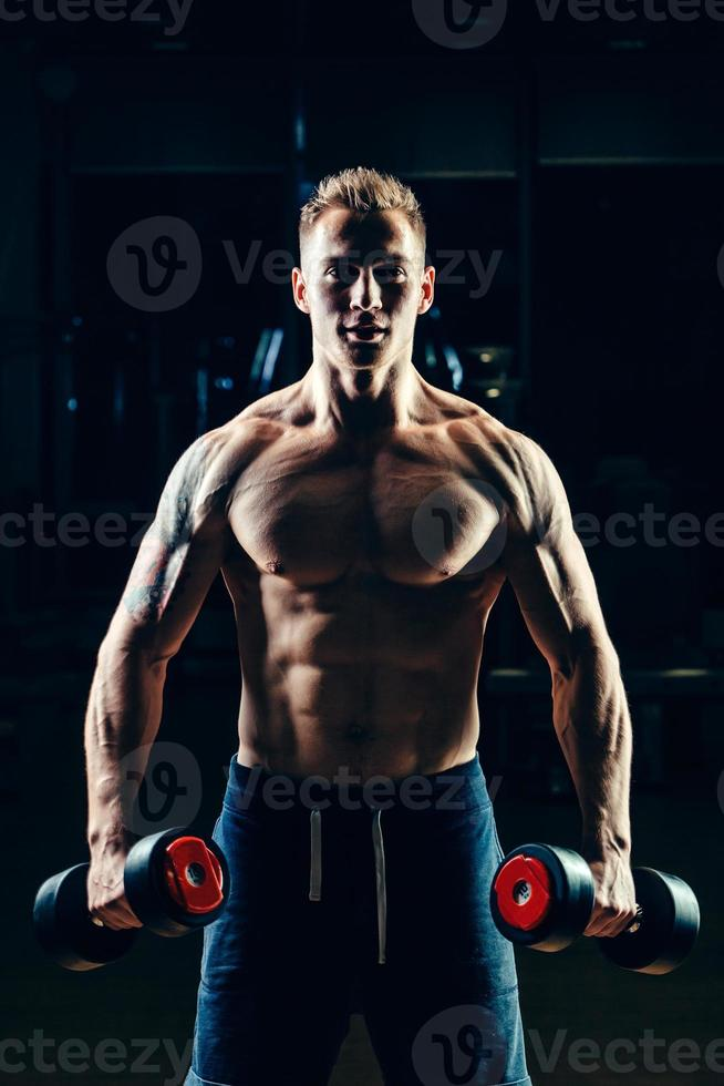 Athlete muscular bodybuilder training back with dumbbell  in the gym photo