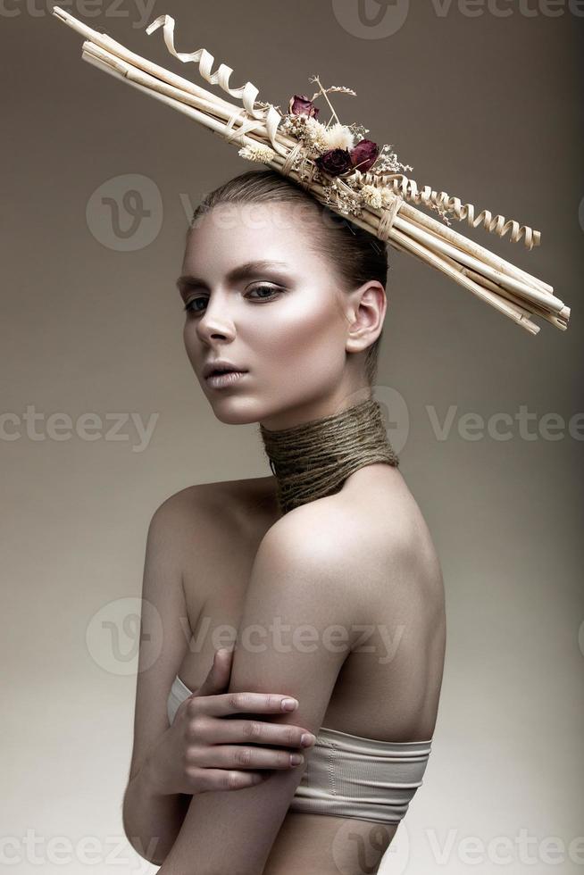 hermosa chica con piel bronceada, maquillaje pálido y accesorios inusuales. foto