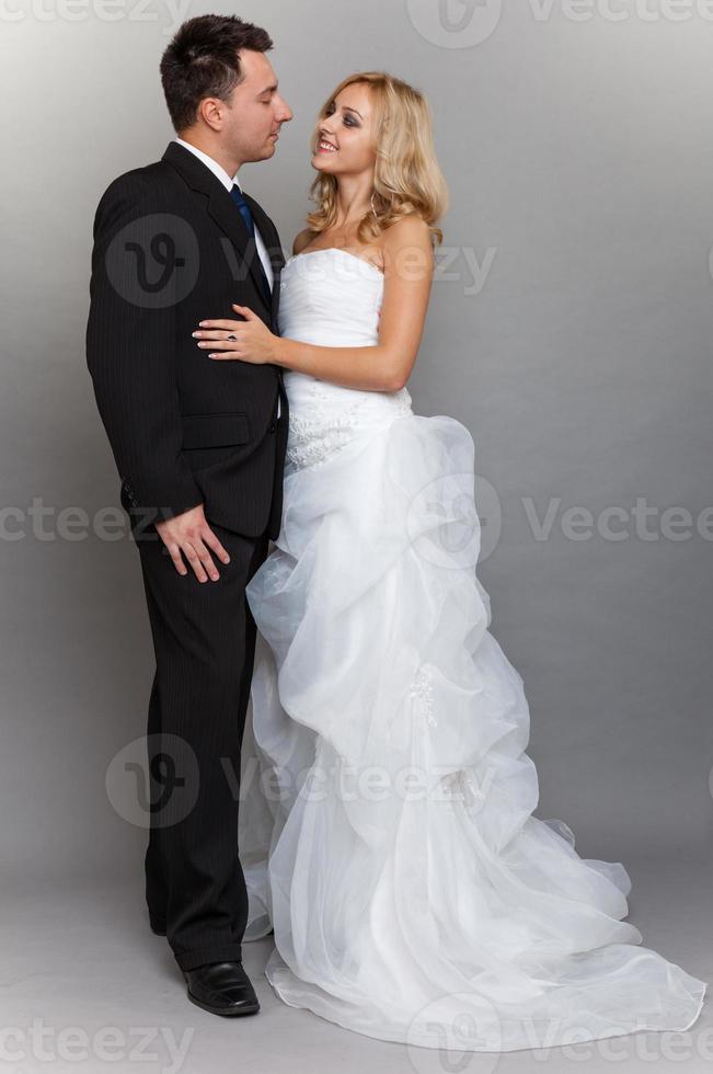 feliz pareja casada novia novio sobre fondo gris foto