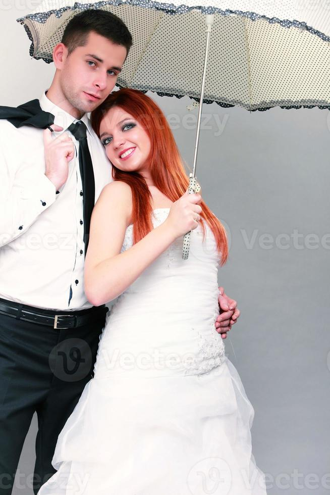 Happy married couple bride groom on gray background photo