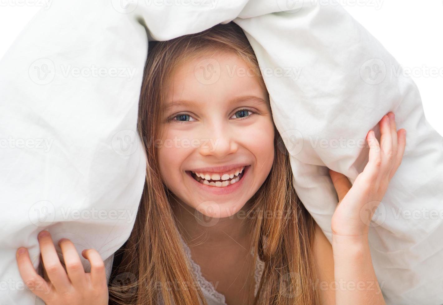 niña riendo debajo de una manta foto