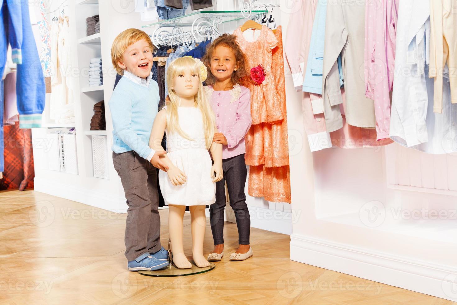 Niño y niña riendo de pie con muñeca maniquí foto