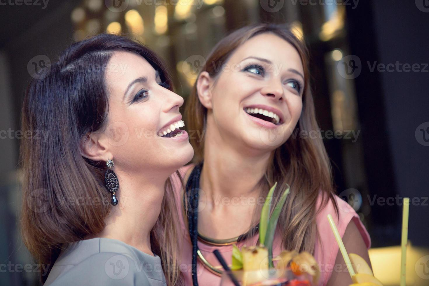 Young laughing female friends have fun at cocktail party photo
