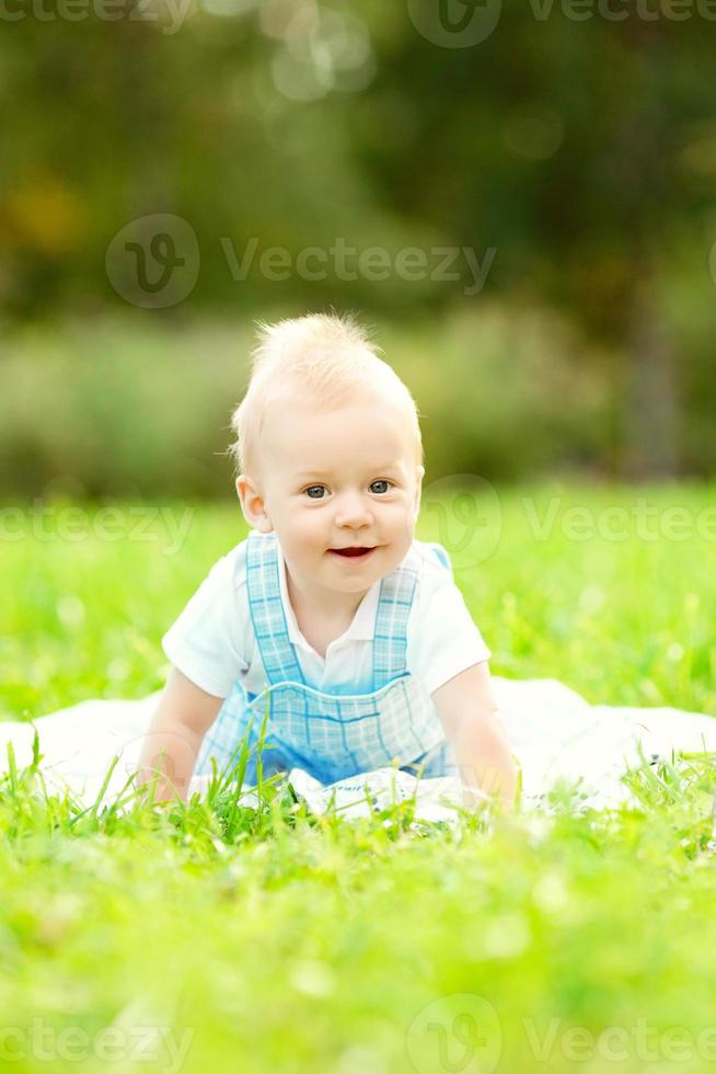 Cute little baby in summer  park on the grass. photo
