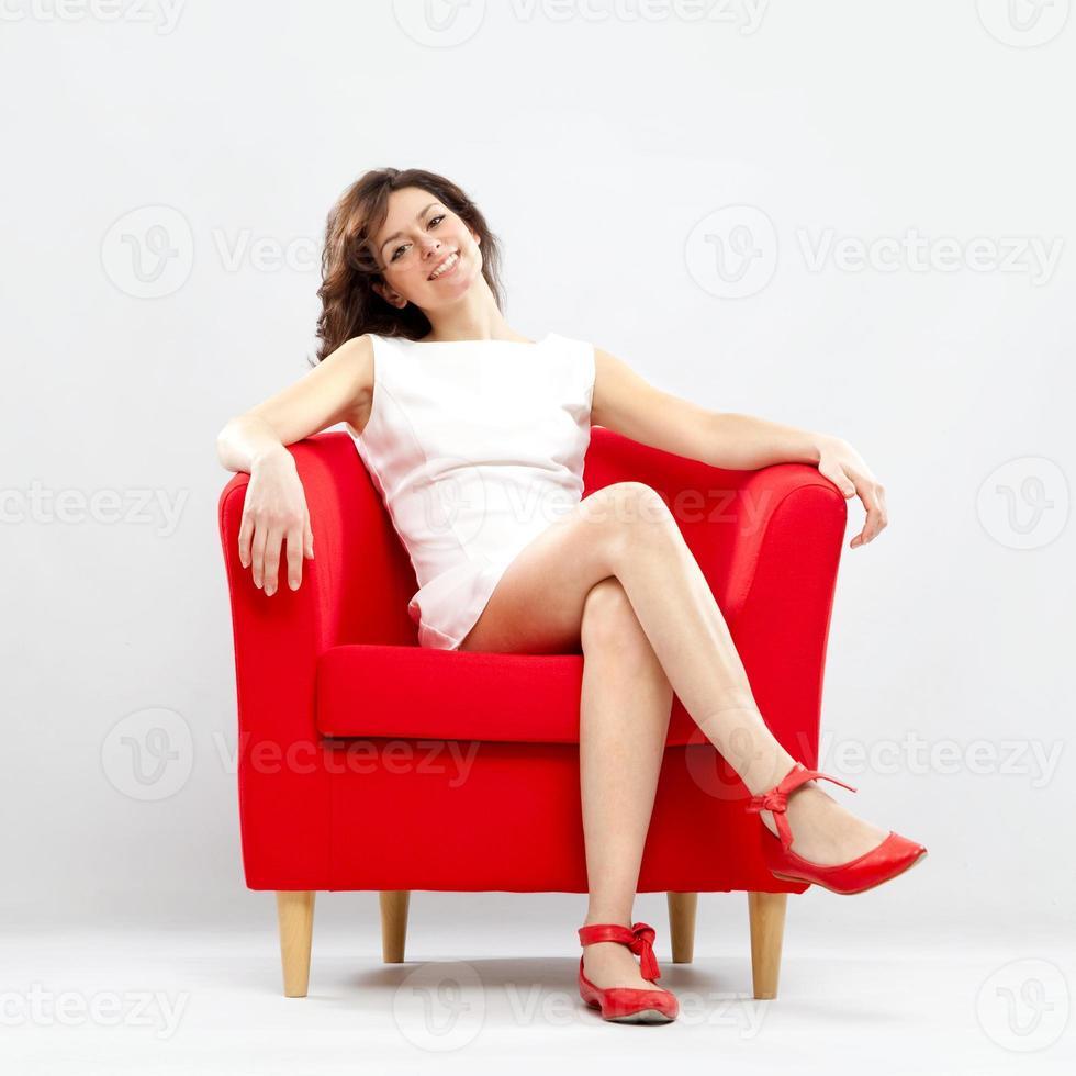 hermosa niña sonriente relajada en sillón rojo foto