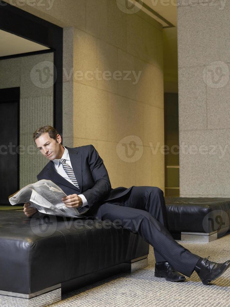 empresário relaxado lendo jornal no lobby do escritório foto