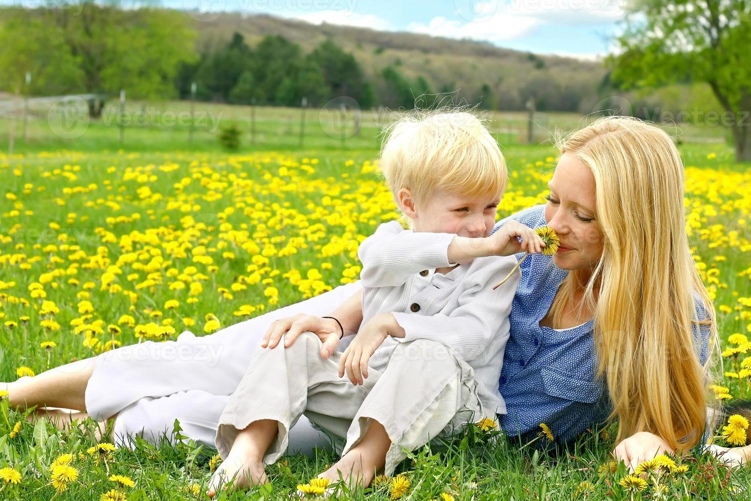 madre y niño pequeño relajante en prado de flores foto