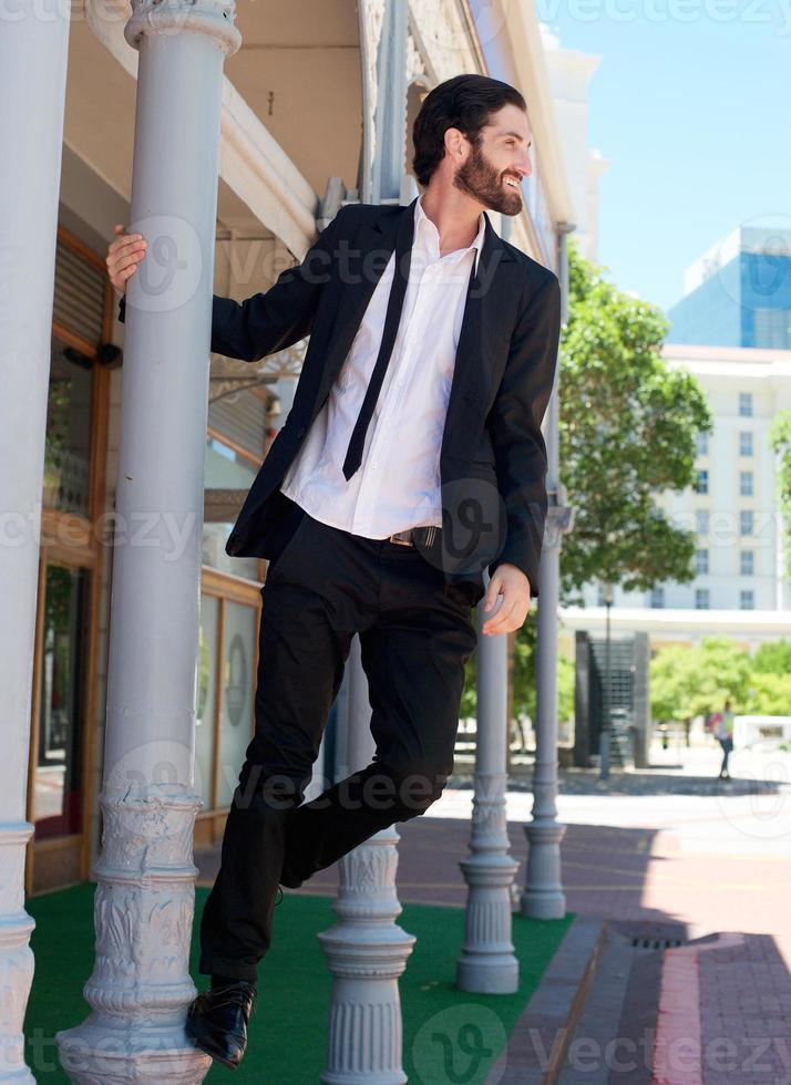 Happy relaxed businessman holding on to pole outside photo