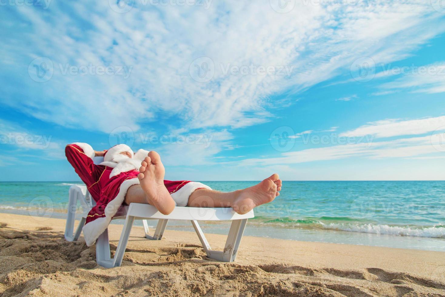 sunbathing Santa Claus relaxing on tropical sandy beach photo